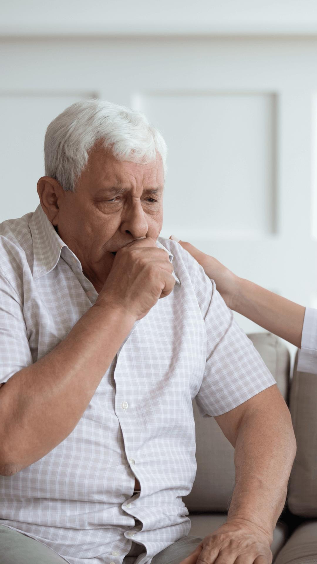 an older man coughing